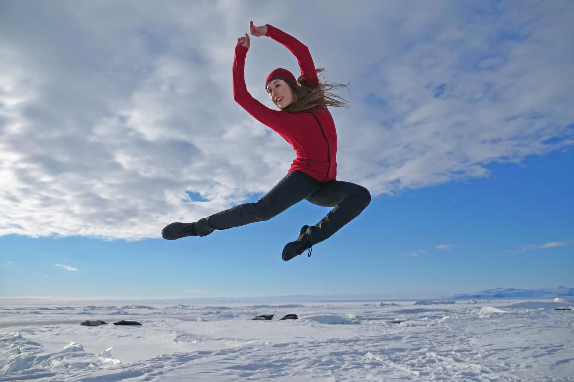 Dancer, Madeleine Graham jumping with Antartic landscape in the background.